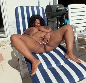 Cheerful ebony BBW playing with her huge juggs outdoor